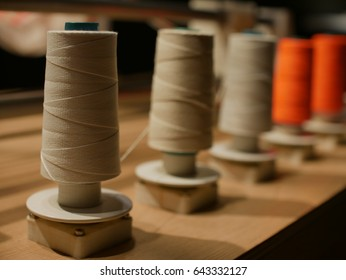 spools of thread display on wood table in factory