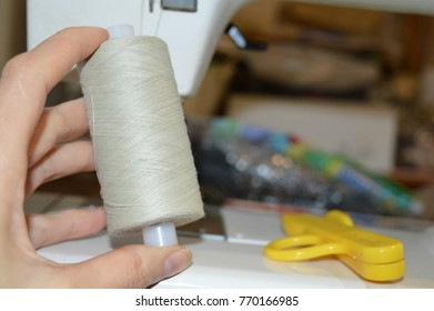Spools of thread in the hands of seamstresses. Thread the sewing machine.