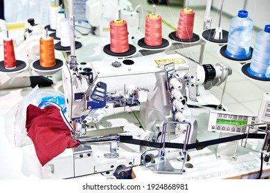 Spools of thread and sewing coverstitch machine. Collarette attaching