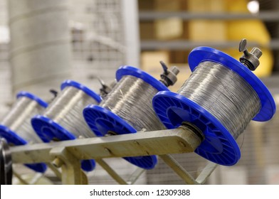 Spools of wire on a stitching machine in a printing plant