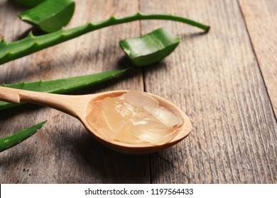 Spoon with aloe vera gel on wooden background