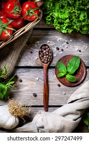 Spoon with black pepper spice, mint, tomato and green salad on the wooden table in the kitchen