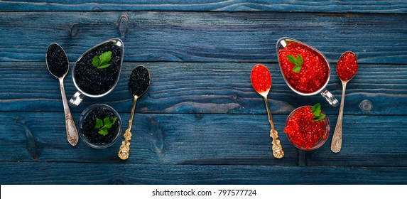 Spoon with black and red caviar on a wooden background. Top view. Free space for text.