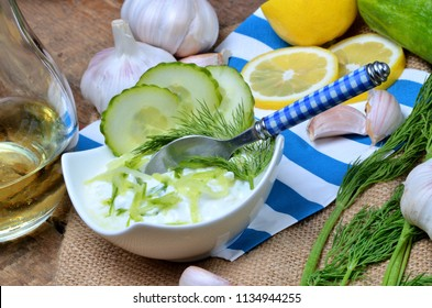 Spoon in bowl with Tzatziki - traditional Greek dressing or dip sauce, garlic, lemon, dill, cucumber, jug with oil and decoration in background