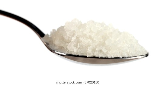 A spoon of coarse sea salt against a white background, extreme close-up
