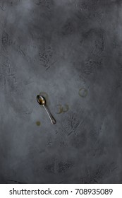 A spoon and coffee stains on a concrete background