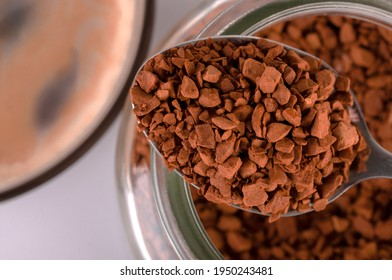 The spoon contains dry granules of instant coffee. A coffee drink is poured into the cup.