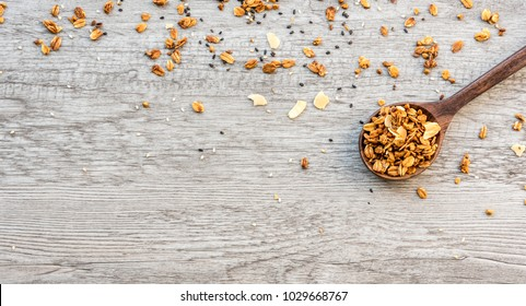 Spoon with crunchy granola or muesli scattered healthy diet breakfast, top view wooden background.