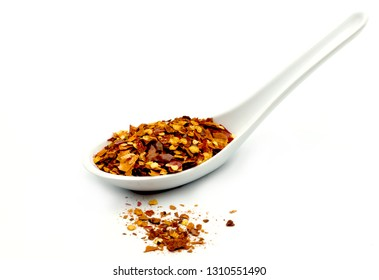 A spoon of crushed dried red hot chili pepper on white background