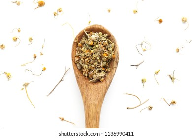Spoon with dried chamomile flowers on white background