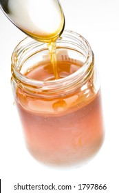 Spoon drizzling honey into a jar