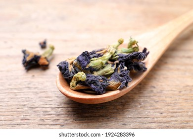 Spoon with dry organic blue Anchan on wooden table, closeup. Herbal tea
