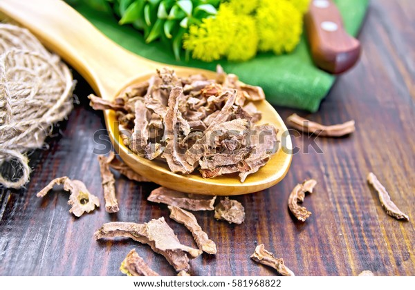 Spoon the dry root of Rhodiola rosea, knife, fresh flowers, a skein of twine on a wooden boards background
