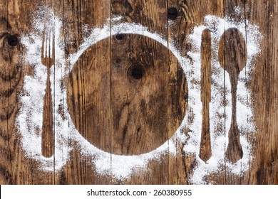 Spoon and fork, flour sprinkled around the wooden plank.