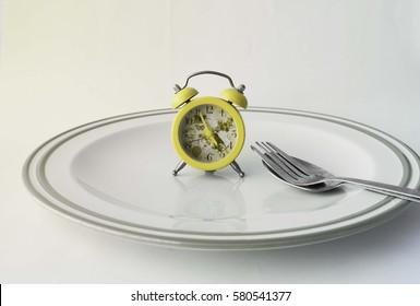 Spoon, Fork with green alarm clock on plate, isolated on white background ,vintage style in morning sunlight.