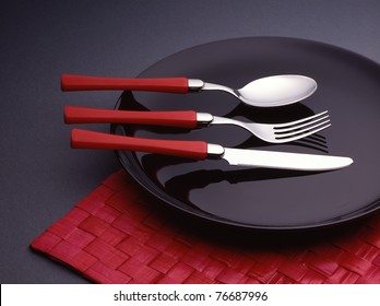 Spoon, fork and knife on a black plate.