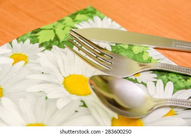 spoon, fork and knife on the table cloth on wooden table