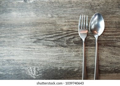 Spoon and fork on brown wooden surface, empty space on the right, view from above.