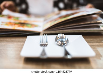 Spoon and fork on the dish with hand of women reading the food menu.