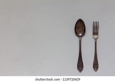 spoon and fork on a white concrete background