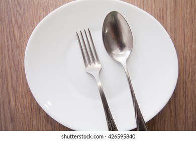 The spoon, a fork, a plate lying on a wooden table