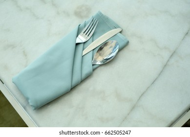 spoon and fork tied on a blue napkin on marble table