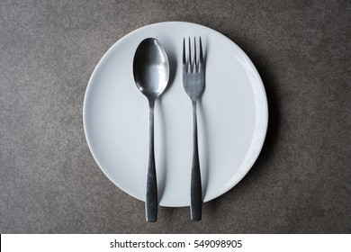 Spoon and Fork Tied on a White Napkin on Wooden Table