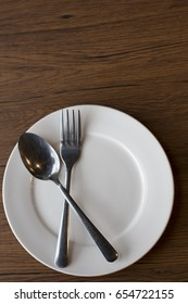 spoon and fork and white dish on wood table , concept eating.