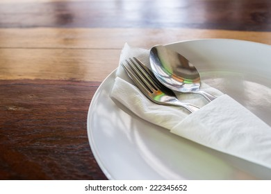 spoon and fork in the white plate with table wood background
