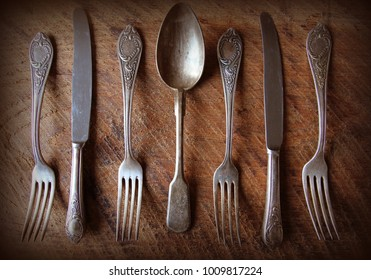 Spoon, forks, knives, ladles on a wooden table, selective focus and toned image. Top view