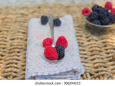 A spoon of fresh blackberries over antique lace napkin and  wicker background. Space for your text.