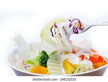 Spoon fresh salad in white plate isolated white background.