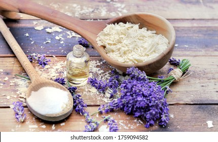 spoon full of flakes of soap with essential oil and bunch od lavender flowers and sodium bicarbonate on wooden background