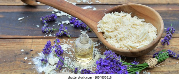 spoon full of flakes of soap with essential oil and lavender flowers on wooden background