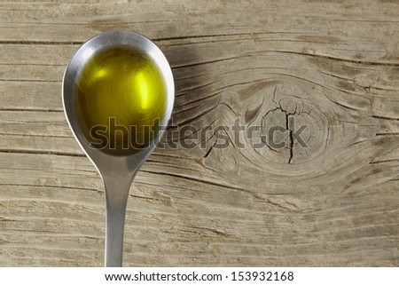 spoon full of olive oil on a wooden table