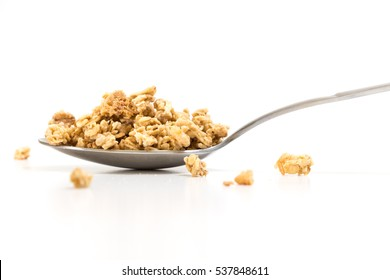 Spoon with granola, on white background.