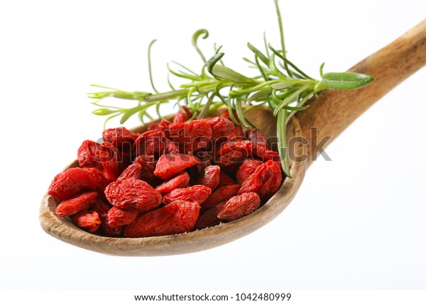 spoon of healthy goji berries on white background