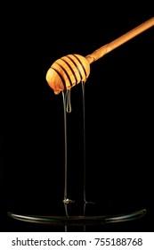Spoon of honey. On a black background. Dripping fresh honey.