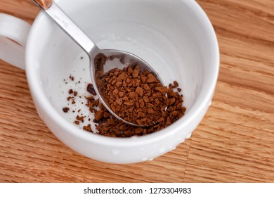 Spoon with instant coffee inside of a cup. Close up.