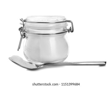Spoon and jar with baking soda on white background