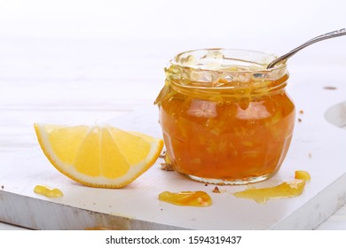 Spoon in a jar of jam. Orange jam on a white wooden background
