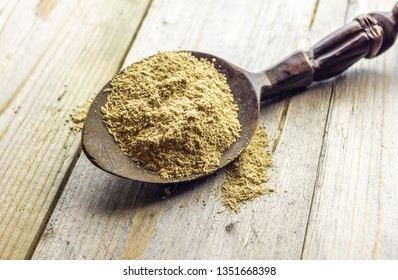 Spoon with Kava Kava root powder on wooden table - Shutterstock ID 1351668398