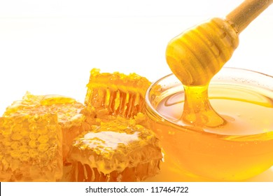 a spoon is kept in a pot of honey. isolated against white background
