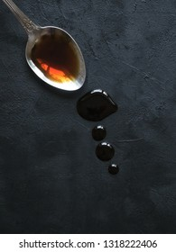 Spoon with leaking soy sauce on the black table. Puddle of soy sauce.