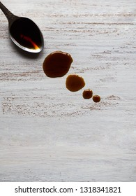 Spoon with leaking soy sauce on the white wooden table. Puddle of soy sauce.