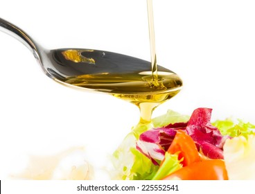 spoon with olive oil on italian fresh salad on white background nutrition concept