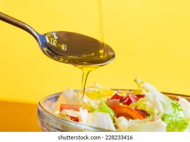 spoon with olive oil on italian fresh salad on yellow light tint background diet concept