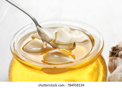Spoon over glass jar with honey and garlic, closeup