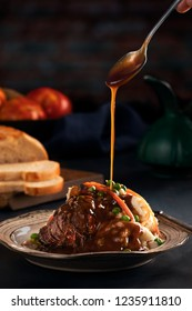 Spoon pouring  gravy on to a pot roast with mashed potatoes, sweet peas and shredded carrots on dark rustic background with bread and tomatoes.