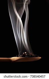 Spoon with roasted coffee loosening smoke.